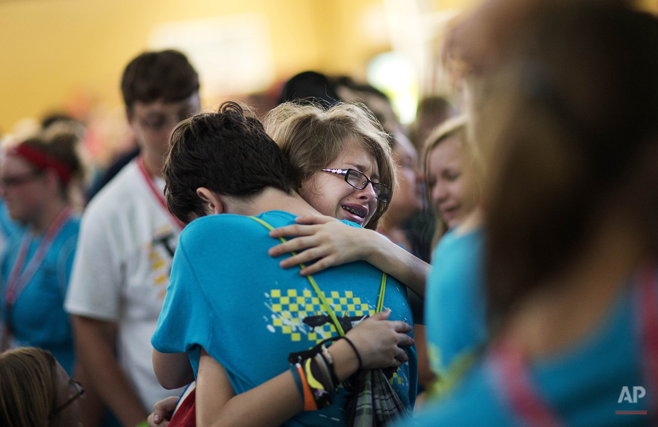 "In this Friday, July 18, 2014 photo, Kristin Moorehead, 13, of Tampa, Fla., right, says goodbye to A.J. Dorough, 13, of Covington, Ga., as they leave to go home from Camp Twitch and Shout, a camp for children with Tourette's Syndrome in Winder, Ga. Dorough and Moorehead first met at the camp four years ago and have attended the annual dance together held on the camp's final night ever since. ""I try to be tough when we say goodbye after camp ends but as soon as I get into the car, I start crying,"" says Dorough. Through sharing experiences, the children learn to better cope with Tourette's while forming strong friendships. For many, the biggest challenge is leaving. (AP Photo/David Goldman)"