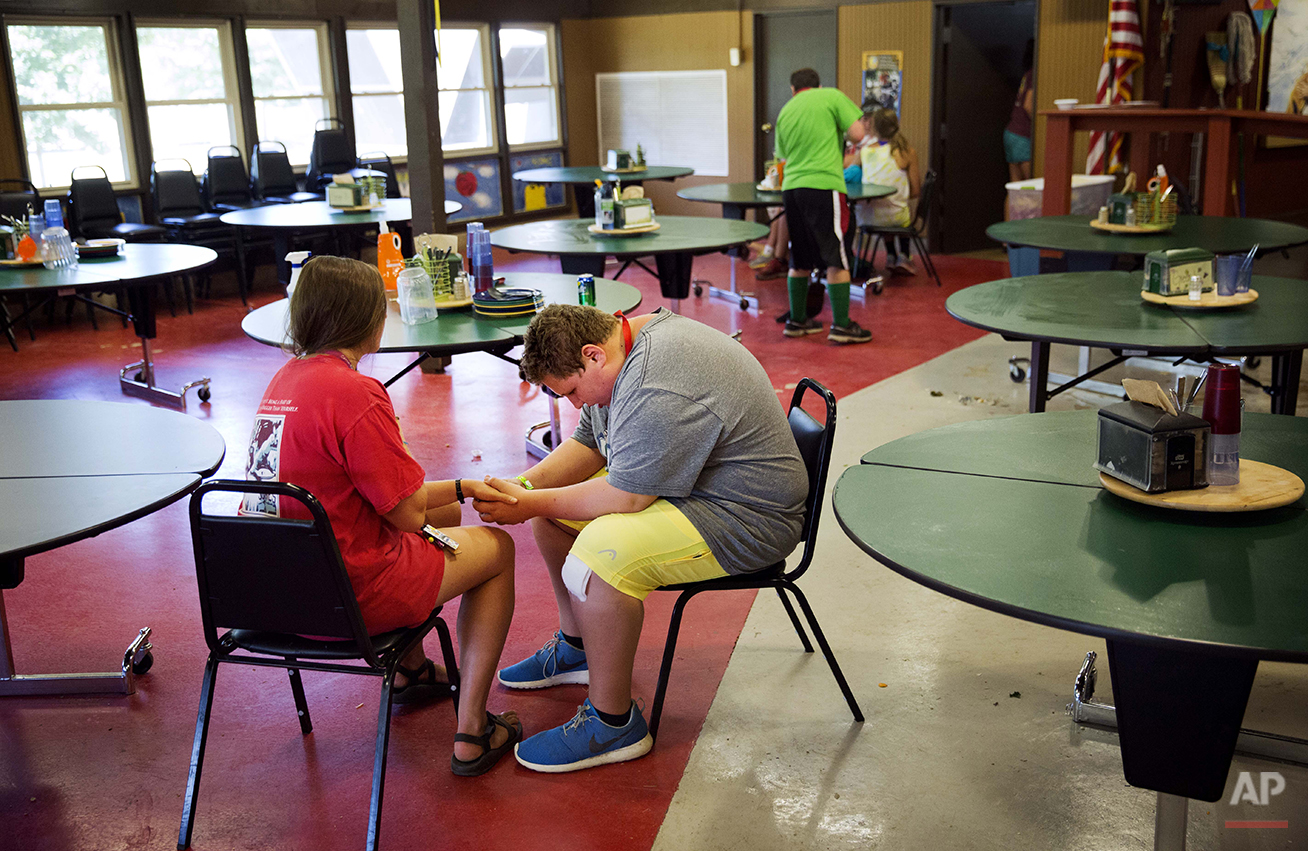 In this Thursday, July 17, 2014 photo, camper Andrew Nail, 14, of Atlanta, right, sits with counselor Danielle Kaidon, 21, as she helps him get through a tic where he feels the urge to hold someone's hand following lunch hour at Camp Twitch and Shout, a camp for children with Tourette's Syndrome in Winder, Ga. The two sat there for about ten minutes until Nail felt the urge pass. (AP Photo/David Goldman)