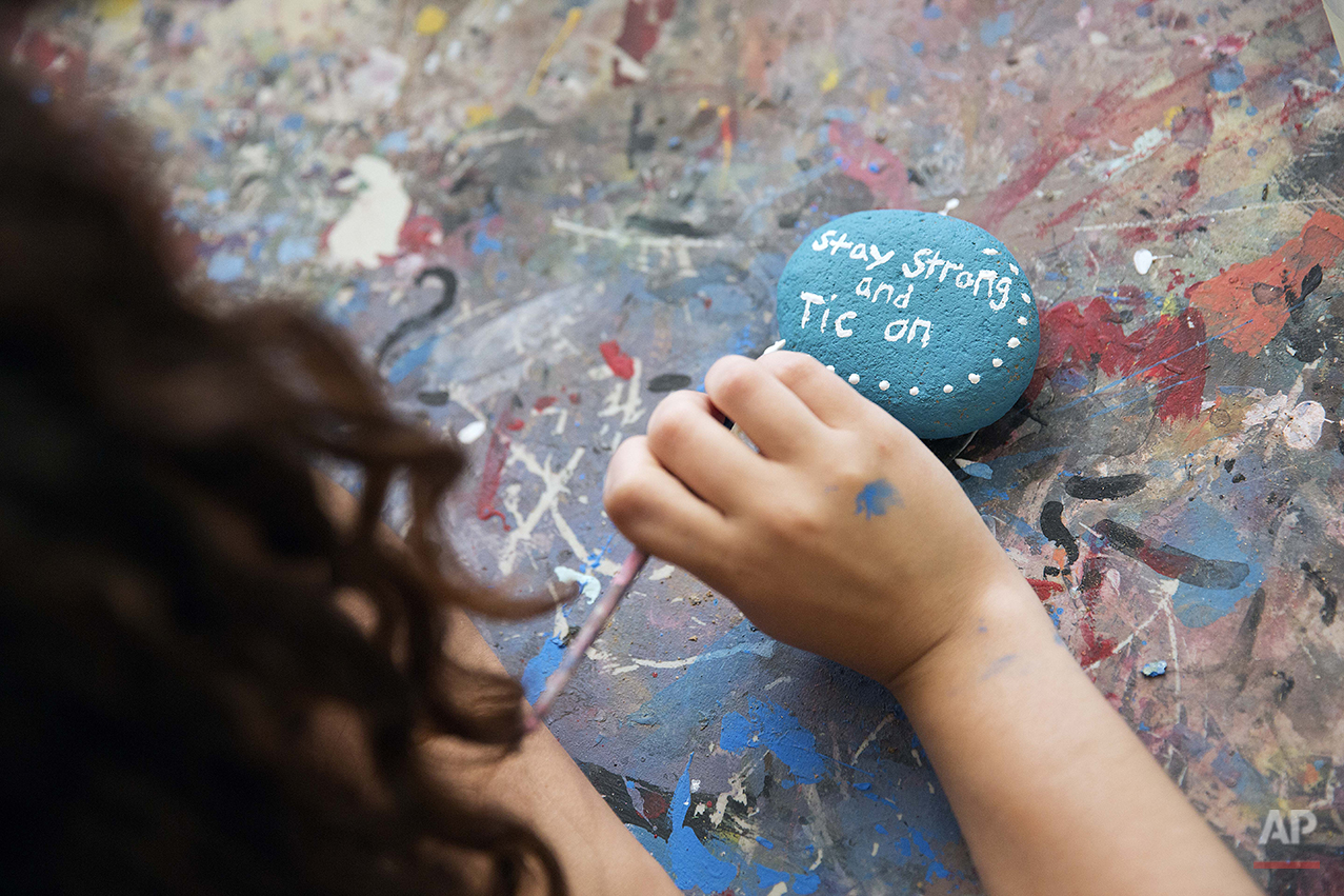 In this Thursday, July 17, 2014 photo, counselor in training Audrey Vogel, 18, of Monroe, Conn., paints a rock with a message on it during an art activity at Camp Twitch and Shout, a camp for children with Tourette's Syndrome in Winder, Ga. (AP Photo/David Goldman)