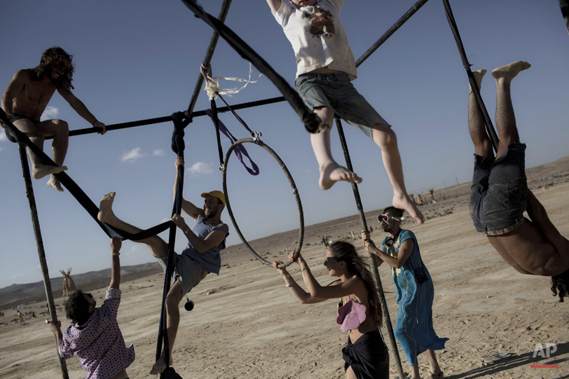 """In this photo taken Friday, June 6, 2014, Israelis climb on one of the art installation during Israelís first Midburn festival, modeled after the popular Burning Man festival held annually in the Black Rock Desert of Nevada, in the desert near the Israeli kibbutz of Sde Boker. Some 3,000 people set up a colorful encampment in the dusty moonscape, swinging from hoops by day and burning giant wooden sculptures by night. For five days, participants mostly Israelis created a temporary city dedicated to creativity, communal living, and what the festival calls ìradical self-expression"""". (AP Photo/Oded Balilty)"""