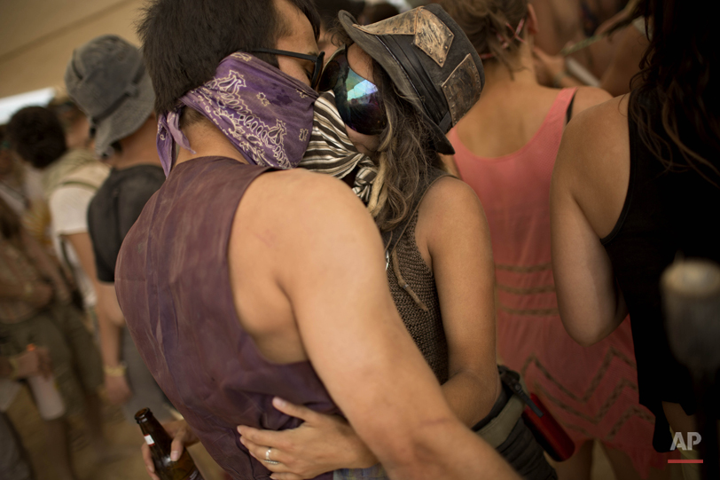 """In this photo taken Thursday, June 5, 2014, Israelis kiss at a party during Israelís first Midburn festival, modeled after the popular Burning Man festival held annually in the Black Rock Desert of Nevada, in the desert near the Israeli kibbutz of Sde Boker. Some 3,000 people set up a colorful encampment in the dusty moonscape, swinging from hoops by day and burning giant wooden sculptures by night. For five days, participants mostly Israelis created a temporary city dedicated to creativity, communal living, and what the festival calls ìradical self-expression"""". (AP Photo/Oded Balilty)"""