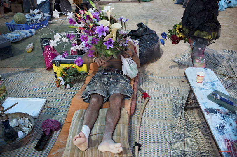 """In this photo taken Saturday, June 7, 2014, an Israeli man holds flowers during Israelís first Midburn festival, modeled after the popular Burning Man festival held annually in the Black Rock Desert of Nevada, in the desert near the Israeli kibbutz of Sde Boker.  Some 3,000 people set up a colorful encampment in the dusty moonscape, swinging from hoops by day and burning giant wooden sculptures by night. For five days, participants mostly Israelis created a temporary city dedicated to creativity, communal living, and what the festival calls ìradical self-expression"""". (AP Photo/Oded Balilty)"""