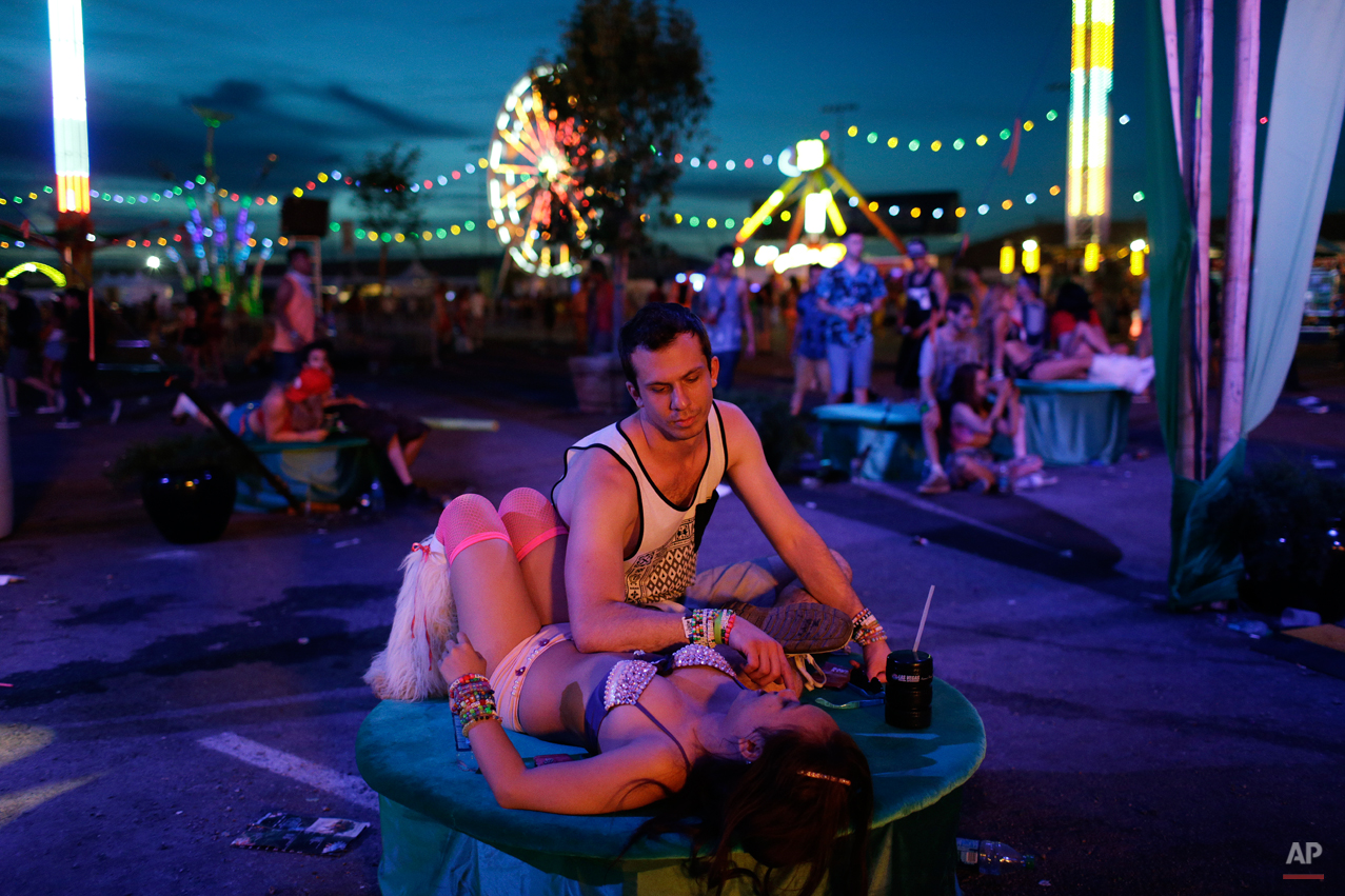 John Cameron and Julia French take a break during the Electric Daisy Carnival, Saturday, June 21, 2014, in Las Vegas. Ample spaces between stages allow festival goers to escape the loud music and pulsating masses of people. (AP Photo/John Locher)