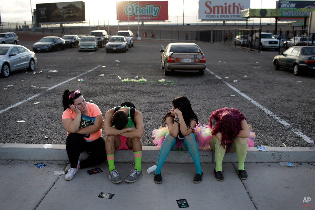 After a long night of partying at the Electric Daisy Carnival, festival goers rest on a curb outside of the Las Vegas Motor Speedway early in the morning on Saturday, June 21, 2014, in Las Vegas. Many of the attendees will return to their home or lodging to rest during the day before returning for another night. (AP Photo/John Locher)