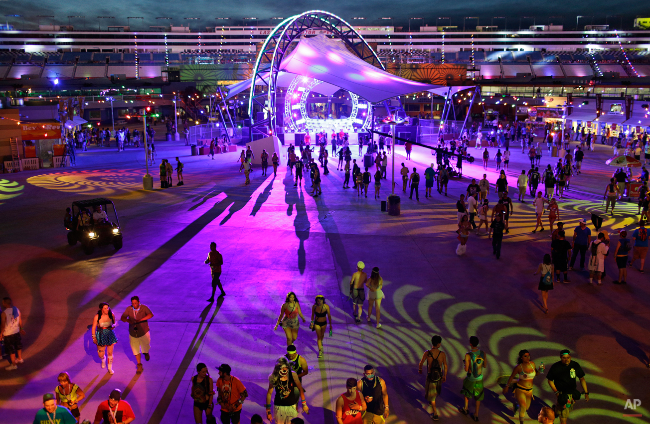 People walk around a stage during the Electric Daisy Carnival, Friday, June 20, 2014, in Las Vegas. People from around the world come to the event to listen to electronic dance music and experience the lights, art installations and carnival rides. (AP Photo/John Locher)