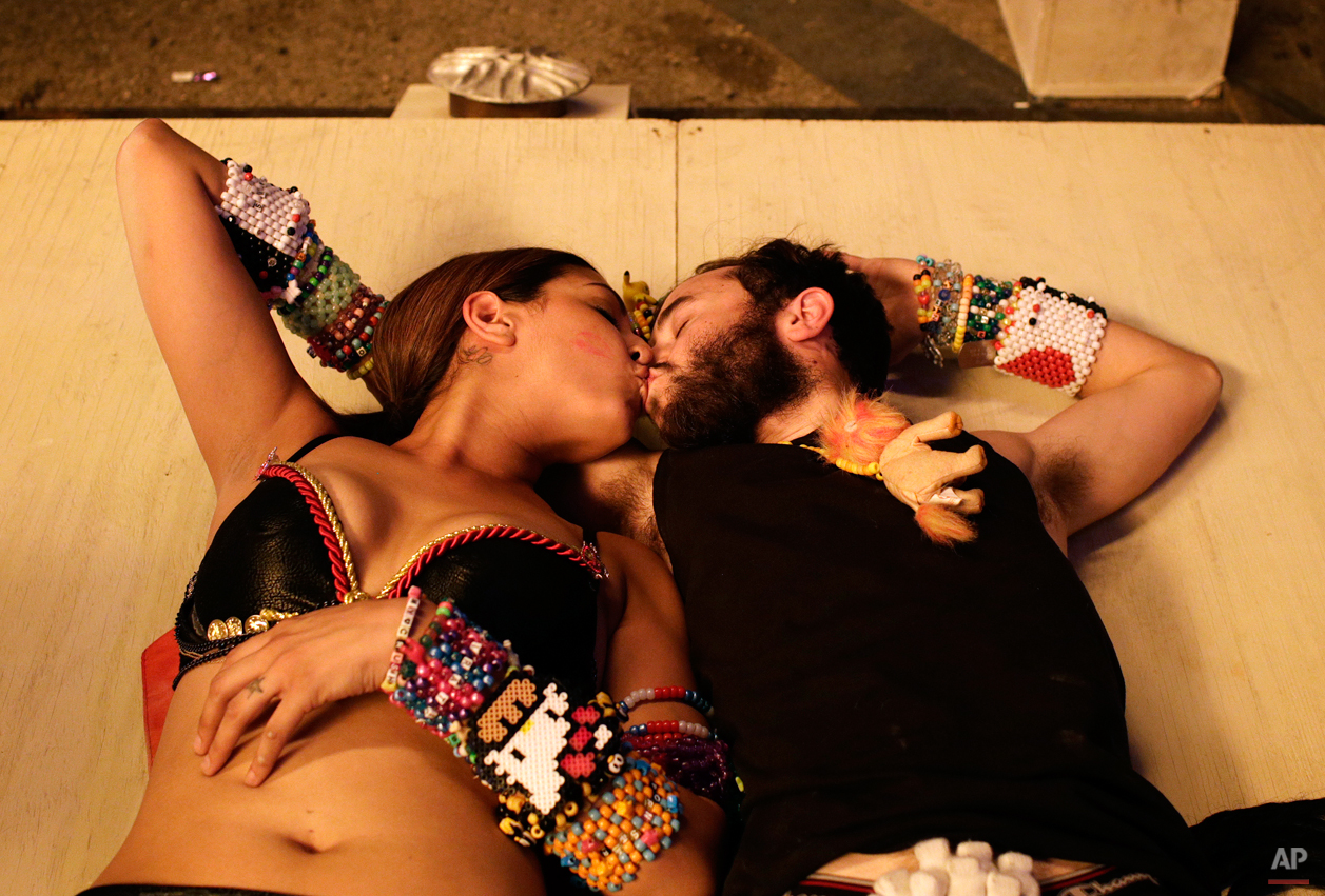 Maggie Sanchez, left, and Chad Wry, both of Riverside, Calif., kiss beneath an art installation at the Electric Daisy Carnival Friday, June 20, 2014, in Las Vegas. (AP Photo/John Locher)