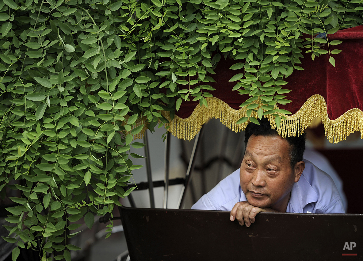 A Chinese man looks out from his trishaw as he waits for customer at a hutong alley near the drum tower in Beijing, China, Wednesday, May 26, 2010. (AP Photo/Andy Wong)