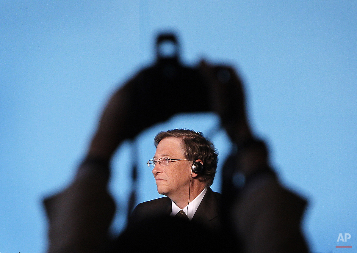 A journalist takes photos of Microsoft Corp. co-founder Bill Gates during a news conference with American billionaire Warren Buffett in Beijing, China Thursday, Sept. 30, 2010. (AP Photo/Andy Wong)