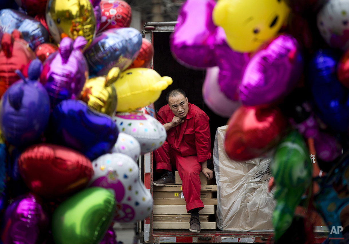 A worker takes a break on a truck loaded with goods in between balloons sold by vendors in Beijing, China Thursday, April 10, 2014. China reported an unexpected contraction in exports in March, raising the danger of job losses as Beijing tries to overhaul its slowing economy. (AP Photo/Andy Wong)
