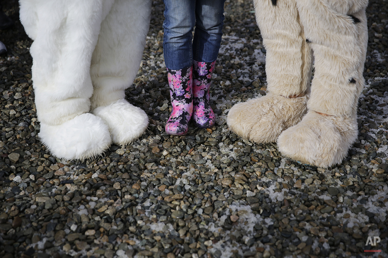 A spectator poses for photos with Sochi Winter Olympics mascots during snowboard parallel giant slalom qualifying at the Rosa Khutor Extreme Park, at the 2014 Winter Olympics, Wednesday, Feb. 19, 2014, in Krasnaya Polyana, Russia. (AP Photo/Andy Wong)