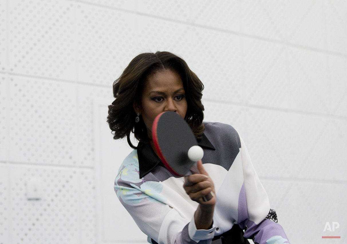 U.S. first lady Michelle Obama plays table tennis at the Beijing Normal School, a school that prepares students to attend university abroad in Beijing, China Friday, March 21, 2014. (AP Photo/Andy Wong, Pool)