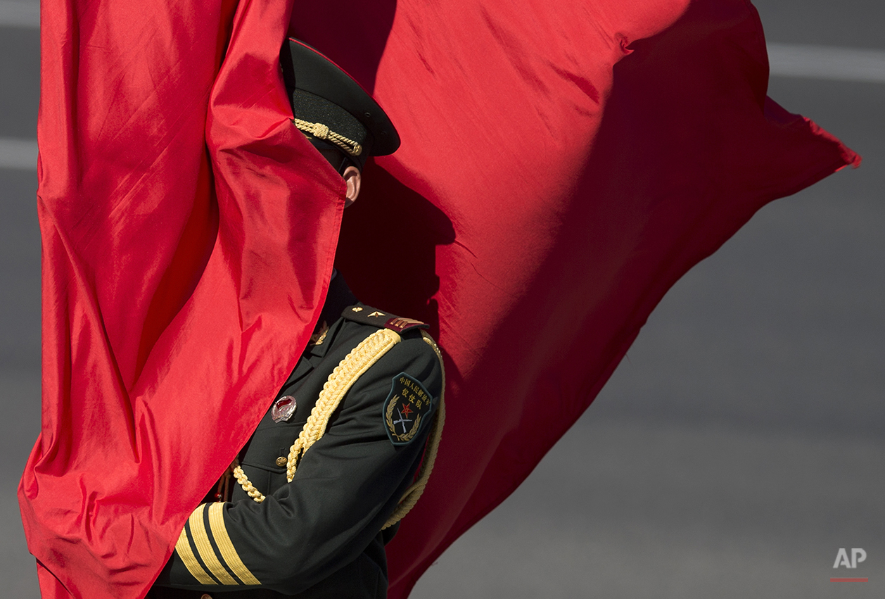A Chinese guard of honor is covered by a red flag as he waits for the arrival of Belarus's President Alexander Lukashenko at a welcoming ceremony at the Great Hall of the People in Beijing, China Tuesday, July 16, 2013. (AP Photo/Andy Wong)