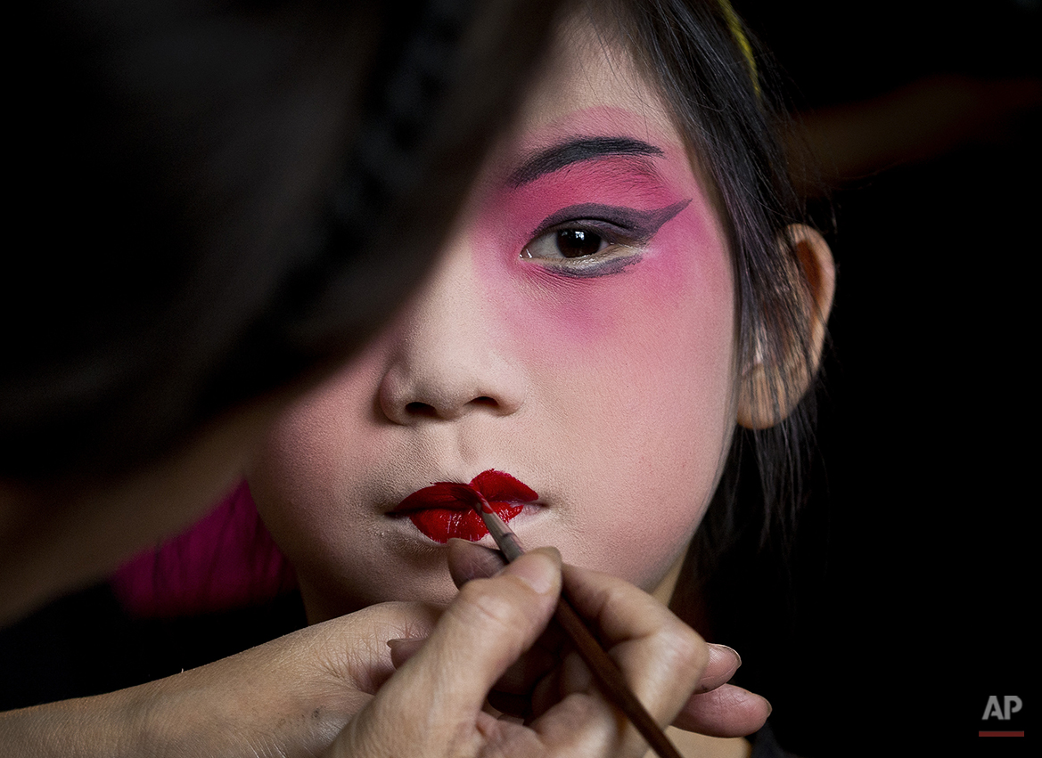 A girl is applied a makeup before a training at Peking Opera summer camp organized by the Peking Opera House in Beijing, China Tuesday, Aug. 14, 2012. The summer training course was held to attract the public to Chinese traditional performance. (AP Photo/Andy Wong)