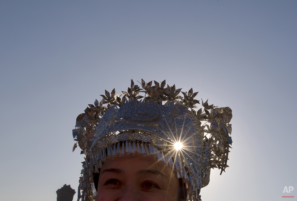 A Chinese ethnic minority delegate wears a traditional costume arrive to the Great Hall of the People to attend the opening session of the annual National People's Congress in Beijing, China, Wednesday, March 5, 2014. (AP Photo/Andy Wong)