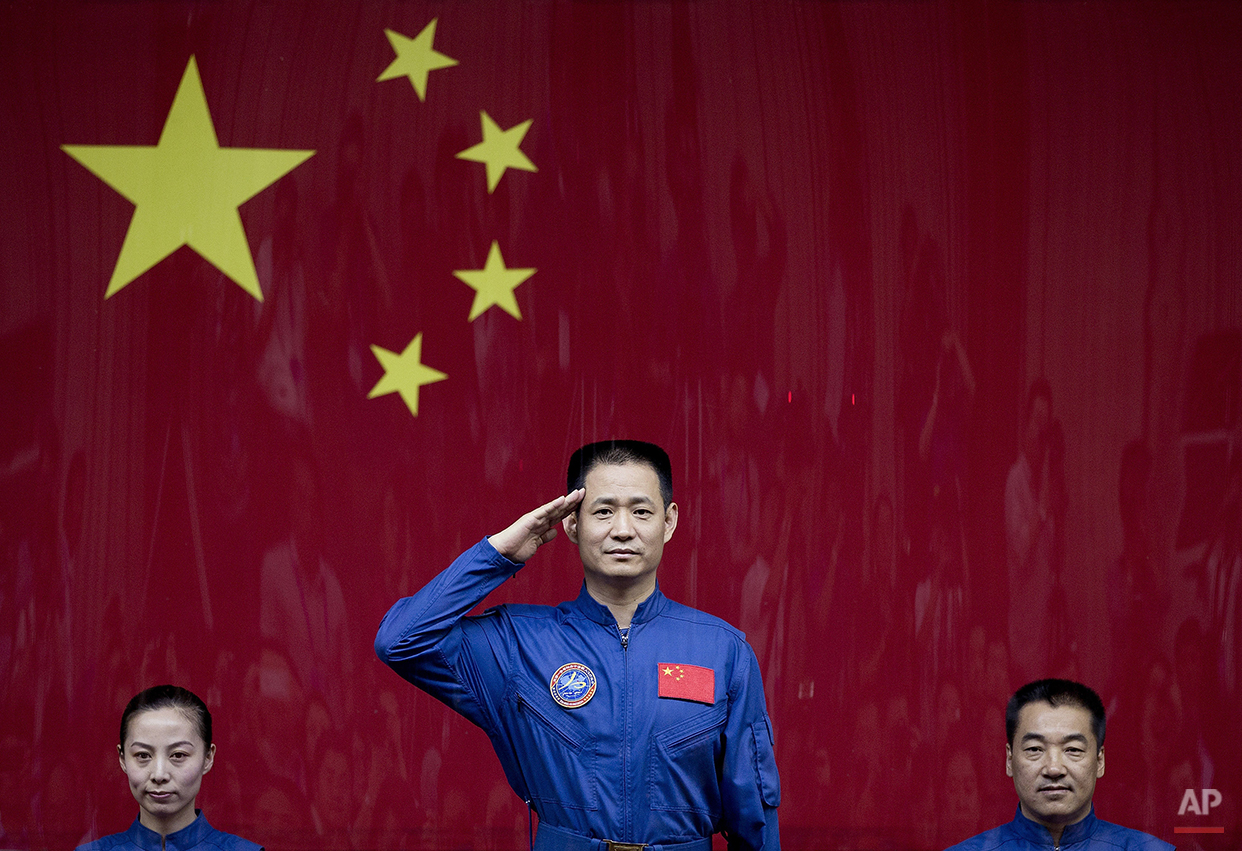 Chinese astronaut Nie Haisheng, center, salutes from behind a glass enclosure next to Wang Yaping, left, and Zhang Xiaoguang, right, as they meet the press at the Jiuquan satellite launch center near Jiuquan in western China's Gansu province, Monday, June 10, 2013. China's astronauts have braved the tension of docking with a space station and performed delicate tasks outside their orbiting capsule, but now face a more down-to-Earth job that is perhaps equally challenging: Talking to young people about science. (AP Photo/Andy Wong)