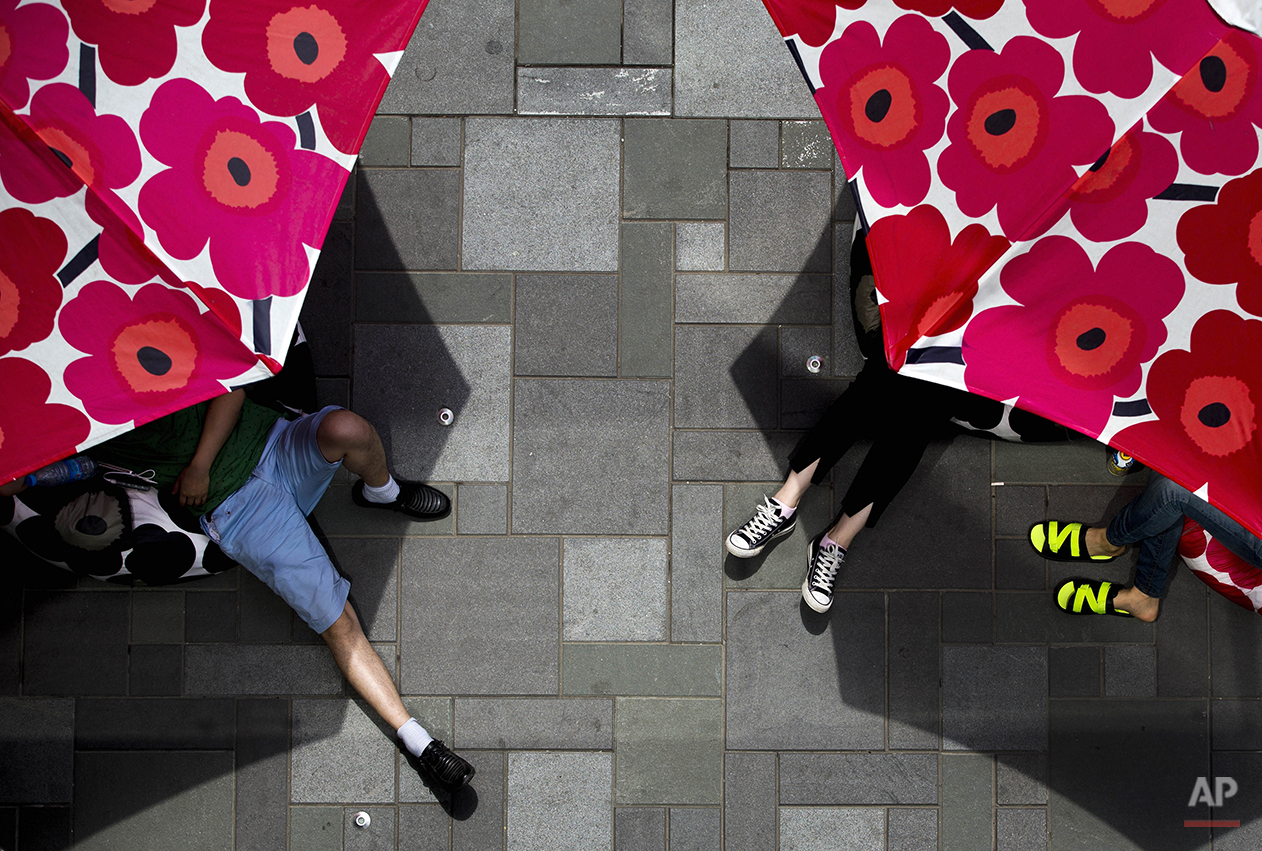 Chinese shoppers take a rest on cushions placed underneath parasols which displayed at a shopping mall as a fashion brand promotion in Beijing Sunday, June 8, 2014. (AP Photo/Andy Wong)