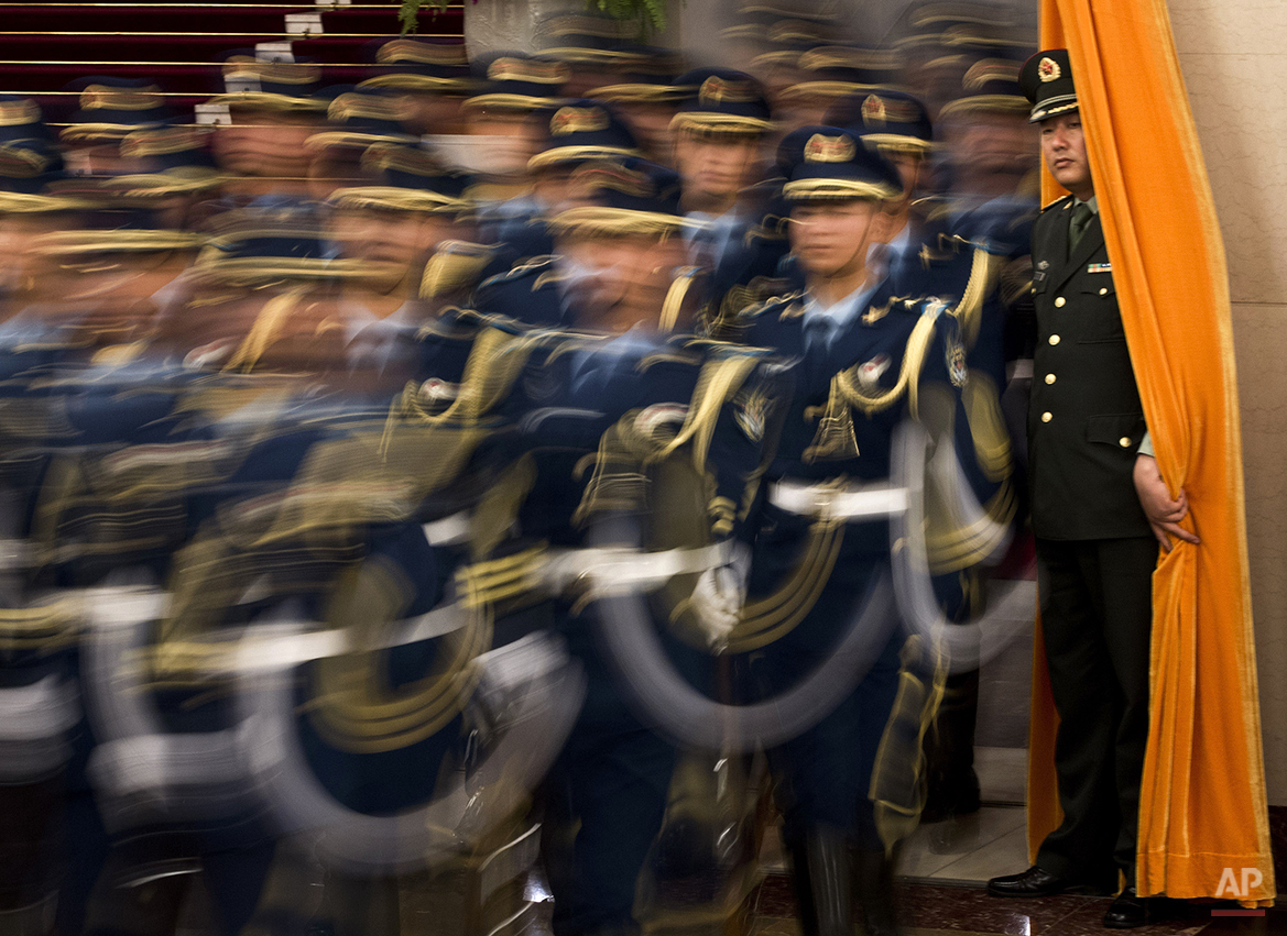 A Chinese military officer watches members of a honor guard march into a hall for a welcome ceremony for Mongolian President Elbegdorj Tsakhia, unseen, at the Great Hall of the People in Beijing Thursday, June 7, 2012. (AP Photo/Andy Wong)