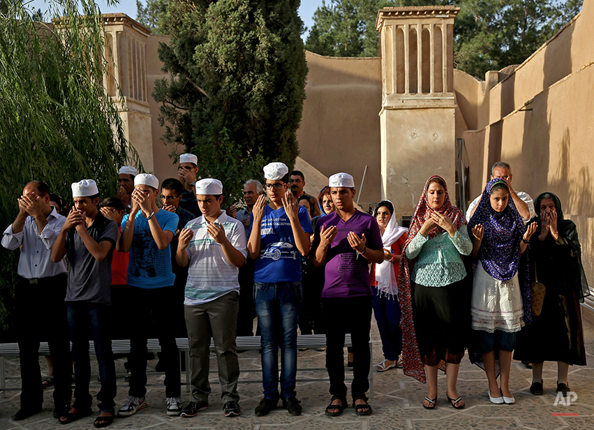 In this Saturday, June 14, 2014 photo, Zoroastrians pray in Setipir Shrine in Yazd about 405 miles (675 kilometers) southeast of the capital Tehran, Iran. Zoroastrianism is a monotheistic religion predating Christianity, Islam and Judaism, founded some 3,800 years ago by the prophet Zoroaster. It was the dominant religion in Persia before the Arab conquest. Thousands of Zoroastrians, like many other Iranians, immigrated abroad under former president Mahmoud Ahmadinejad because of social restrictions and a worsening economy. But now a dozen have returned to live in Iran this past year, the government said. (AP Photo/Ebrahim Noroozi)