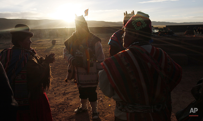 Aymara indigenous men and women attend a new years ritual at the ruins of the ancient civilization of Tiwanaku located in the highlands in Tiwanaku, Bolivia, early Saturday, June 21, 2014. Bolivia's Aymara Indians are celebrating the year 5,522 as well as the Southern Hemisphere's winter solstice, which marks the start of a new agricultural cycle. (AP Photo/Juan Karita)