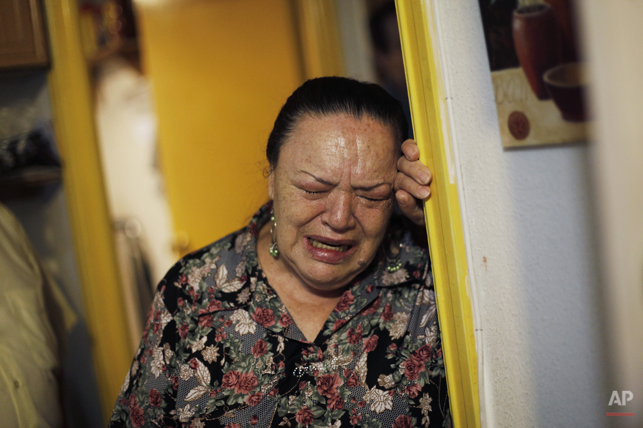 Angeles Romero Fernandez, 65-year old, right, cries as she waits to be evicted in Madrid, Spain, Tuesday July 2, 2013. Romero Fernandez, with a bipolar syndrome, and her husband 68 year-old pensioner Efren Rodriguez Gonzalez, have 6 family members unemployed and a 8 year-old grandchild and have lived together in an apartment of the City Hall Housing Company (EMVS) for 24 years. The eviction was finally postponed until September with the help of the Victims' Mortgage Platform (PAH). (AP Photo/Andres Kudacki)