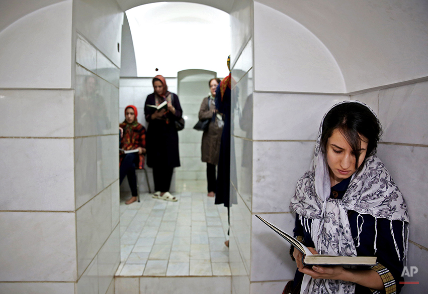 In this Saturday, June 14, 2014 photo, Zoroastrians pray in Setipir Shrine in Yazd about 405 miles (675 kilometers) southeast of the capital Tehran, Iran. Thousands of Zoroastrians, like many other Iranians, immigrated abroad under former president Mahmoud Ahmadinejad because of social restrictions and a worsening economy. But now a dozen have returned to live in Iran this past year, the government said. (AP Photo/Ebrahim Noroozi)