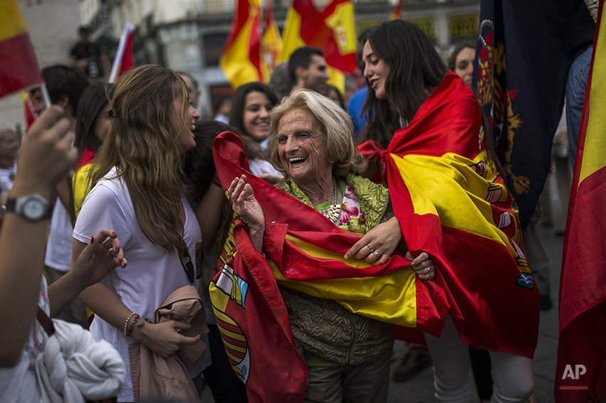 Dozens of demonstrators gather and wave Spanish flags around the monument of Charles III, a former King of Spain, during a demonstration in support of the Spanish Monarchy in the main square of Madrid, Spain, Friday, June 6, 2014. King Juan Carlos plans to abdicate and pave the way for his son, Crown Prince Felipe, to become the country's next king. The 76-year-old Juan Carlos oversaw his country's transition from dictatorship to democracy but has had repeated health problems in recent years. His popularity also dipped following royal scandals, including an elephant-shooting trip he took in the middle of Spain's financial crisis that tarnished the monarch's image. (AP Photo/Andres Kudacki)