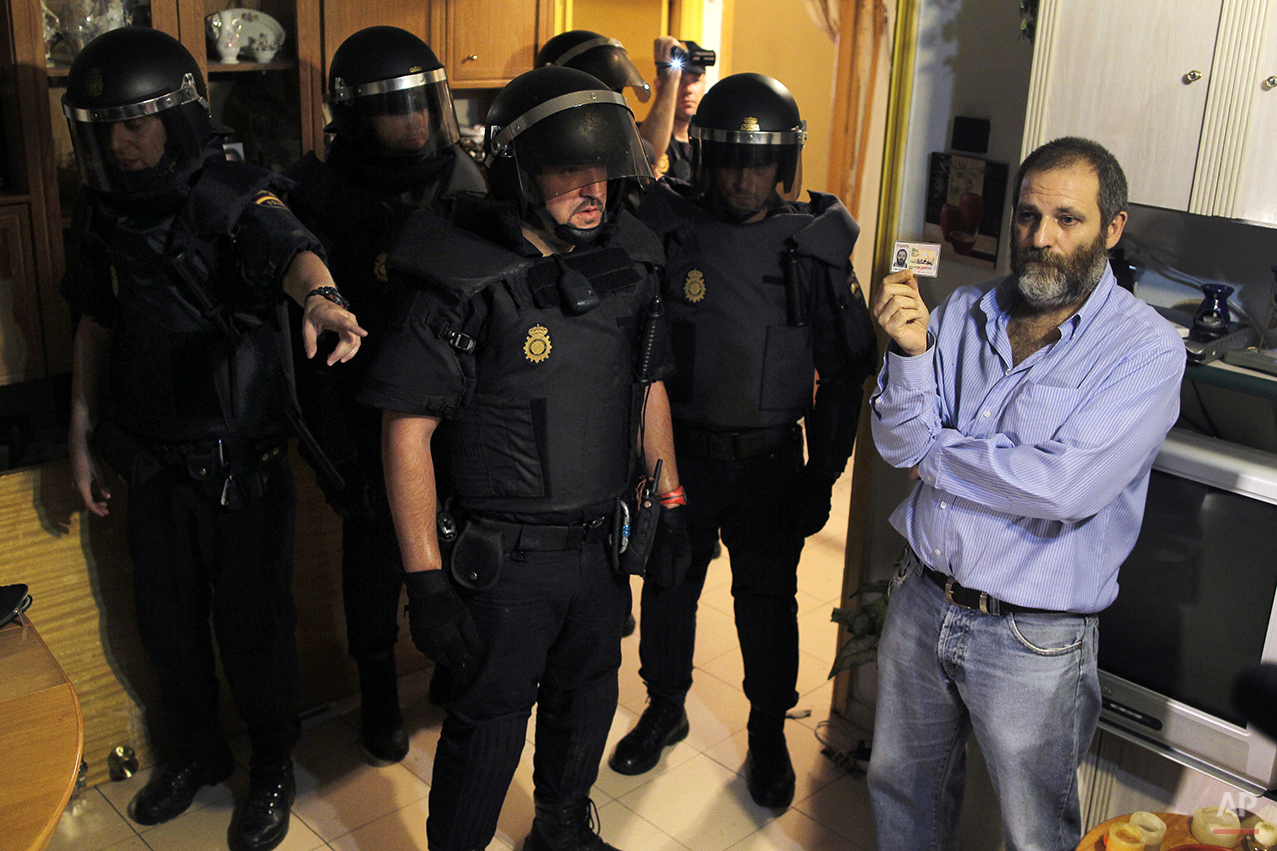 A Victims' Mortgage Platform (PAH) member stands with his ID as police identify activists and media and clear Maria Isabel Rodriguez Romero's apartment during her and her family eviction in Madrid, Spain, Wednesday, Sept. 25, 2013. Forty-five year-old Rodriguez Romero, has 6 family members, all unemployed including an 8 year-old daughter, and her mother with a bipolar syndrome. They live together in an apartment of the State City Hall Housing Company (EMVS) for 24 years and they have paid a debt of 1,200 euros but EMVS informed them they have to move out. The eviction was executed despite the resistance of dozens of Victims' Mortgage Platform (PAH) members. (AP Photo/Andres Kudacki)