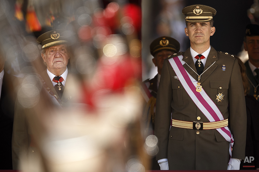 King Juan Carlos and Crown Prince Felipe, right, attend a military ceremony in San Lorenzo de El Escorial, outside Madrid, Spain, Tuesday, June 3, 2014. Spanish Prime Minister Mariano Rajoy is holding an emergency cabinet meeting to draft the legal process for King Juan Carlos to abdicate and be replaced by his son, Crown Prince Felipe. The handover cannot happen until the government crafts the mechanism for abdication and Felipe's assumption of power. The proposal is expected to pass quickly because Rajoy's center-right Popular Party has an absolute majority in Parliament. Juan Carlos led Spain's transition from dictatorship to democracy but was hit by damaging scandals amid Spain's financial meltdown. He announced Monday he was abdicating because his son is ready for the job and Spain needs a 'new era of hope.'(AP Photo/Daniel Ochoa de Olza)