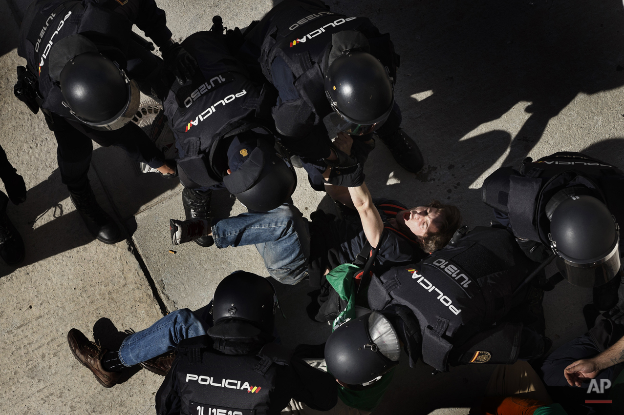 A member of the Victims' Mortgage Platform (PAH) shouts while is carried away by riot police officers as he tried to block the door of Veronica Carro, 51, to prevent her eviction, in Parla, Spain, Wednesday, April 30, 2014. Veronica, a former gardener and concierge at Parla's townhall, has resided in the apartment with her 14 year old daughter Rocio for the past 5 years, but since being unemployed for the last 3 years and her only income was a state handout of 426 euros ($584) a month she could not afford to pay a protected rent of 370 euros a month ($513) to Lazora, a private investor company who bought her house from the City Hall Housing and Land Company (EMVS). Lazora demanded their eviction. (AP Photo/Daniel Ochoa de Olza)