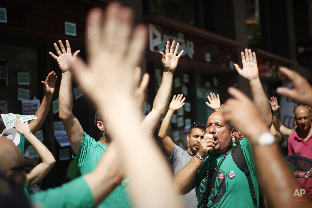 Activists of Mortgage Victims' Platform (PAH) shout slogans against the government before occupying a bank as part of a protest to support a neighbor who is facing an eviction process in Barcelona, Spain, Friday July 26, 2013. With 26 percent unemployment, Spain is struggling to emerge from its second recession in just over three years as the economy battles to recover from the collapse of its once-booming real estate sector.(AP Photo/Paco Serinelli)