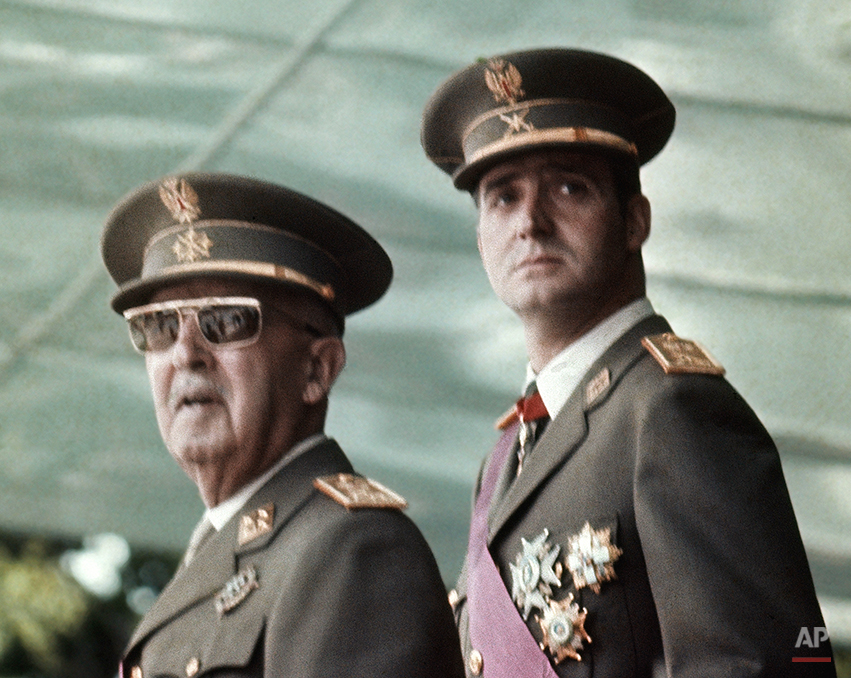 In this May 1973 file photo of Spain's leader Francisco Franco, left, with his future successor as King, Prince Juan Carlos de Borbon, as they watch a military parade in Madrid . Spain's King Juan Carlos will abdicate and pave the way for his son, Crown Prince Felipe, to take over, Spanish Prime Minister Mariano Rajoy told the country Monday in an announcement broadcast nationwide. He did not say when Juan Carlos would abdicate because the government must now craft a law creating a legal mechanism for the abdication and for 46-year-old Felipe's assumption of power. King Juan Carlos came to power in 1975, two days after the death of longtime dictator Francisco Franco. He endeared himself to many Spaniards in large part by putting down an attempted military coup in 1981 when he was a young and largely untested head of state. (AP Photo)