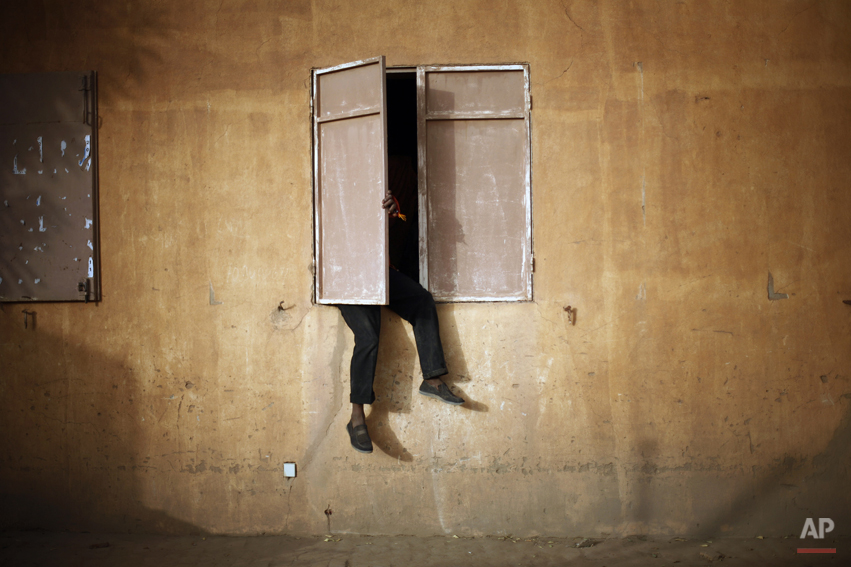 A Malian man sits on a window sill to watch the Nigeria versus Mali Africa Cup of Nations semifinal soccer match taking place in South Africa, in Gao, northern Mali, Wednesday, Feb. 6, 2013. (AP Photo/Jerome Delay)