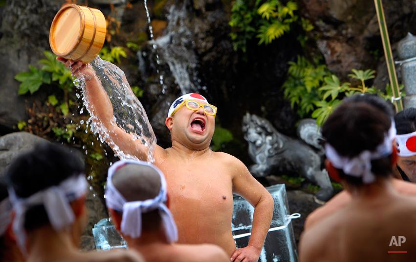 A man braves to splash cold water over himself as other participants watch during a purification ceremony at the Kanda Myojin shrine in Tokyo, Saturday, Jan. 15, 2011.(AP Photo/Junji Kurokawa)