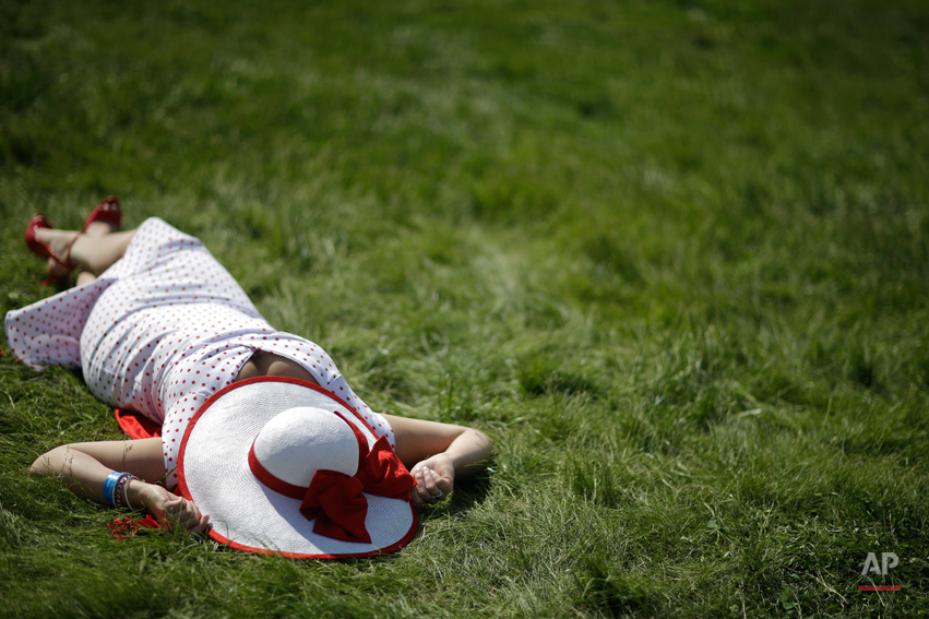 Jaclyn Linde of Madison, Wis. lays in the sun before the 140th running of the Kentucky Derby horse race at Churchill Downs Saturday, May 3, 2014, in Louisville, Ky. (AP Photo/David Goldman)
