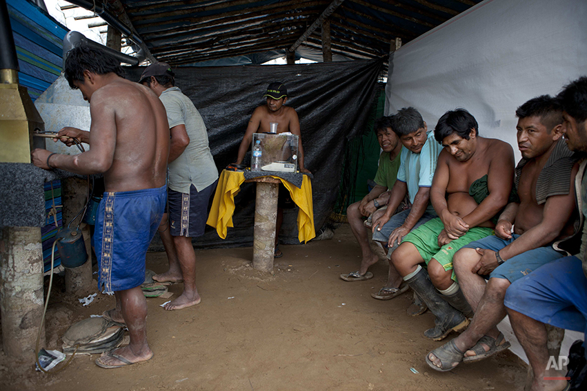 In this May 3, 2014 photo, wildcat miners wait their turn to melt their amalgam of gold and mercury to burn off the mercury in the temporary home of a gold buyer in La Pampa in Peru's Madre de Dios region. It's not just miners who are threatened with economic catastrophe from the government¹s campaign to wipe out illegal mining operations, said a mining camp cook. For every miner there is a family that eats because he works, she said. (AP Photo/Rodrigo Abd)