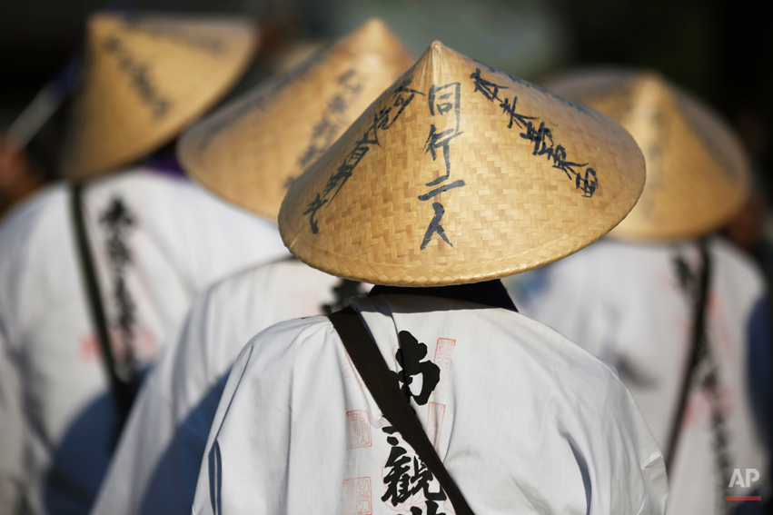 The party of pilgrims walk at Sensoji Buddhist temple at Asakusa district, in Tokyo, Monday, April 14, 2014. Asakusa is an old town in the capital that draws many tourists from across the world. (AP Photo/Eugene Hoshiko)