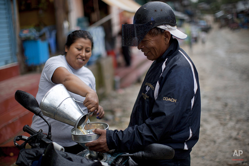 In this May 22, 2014 photo, a vendor fills a man's motorcycle tank with gas because fuel stations are closed in Huepetuhe in the Madre de Dios region of Peru. The government halted gasoline shipments in April and sent troops to destroy heavy machinery used in mining that it deemed illegal as part of a government crackdown. (AP Photo/Rodrigo Abd)