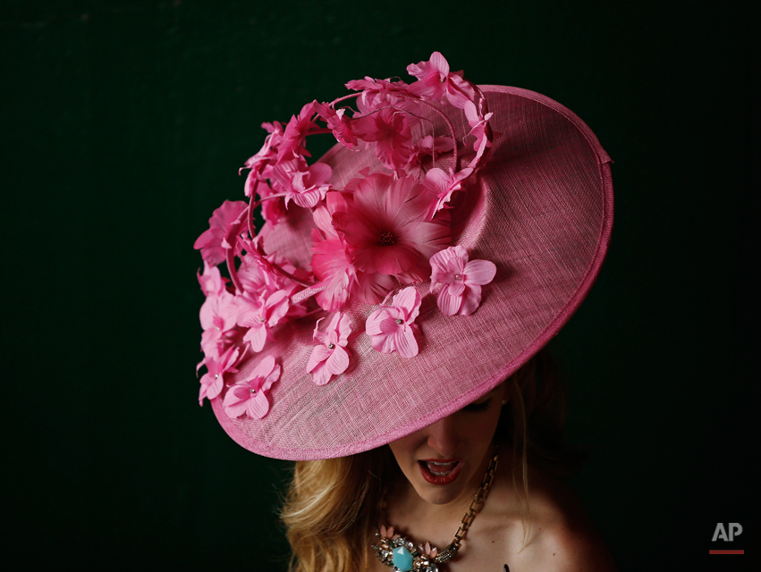 A woman makes her way to the track before the 140th running of the Kentucky Derby horse race at Churchill Downs Saturday, May 3, 2014, in Louisville, Ky. (AP Photo/Matt Slocum)