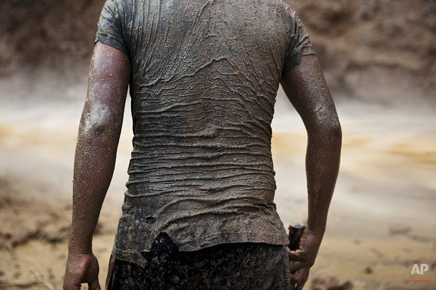 In this May 4, 2014 photo, a miner continues his search for gold in mud-drenched clothes inside a crater at an illegal gold mine process in La Pampa in Peru's Madre de Dios region. The informal miners of La Pampa know they will soon be evicted, their engines blown up and settlements burned after Peru's government declared all informal mining illegal on April 19. The government claims that the informal miners have destroyed the surrounding forests and polluted the environment by using mercury in the gold extraction process. (AP Photo/Rodrigo Abd)
