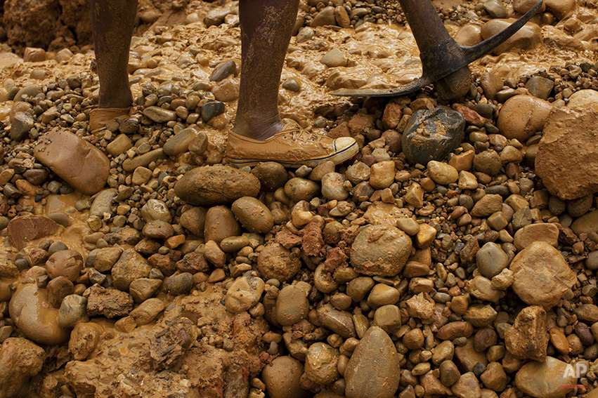 "In this May 21, 2014 photo, a miner with an axe digs for gold using a rustic technique known as ""chiquiquiar"" in Huepetuhe in the Madre de Dios region of Peru. After a government crackdown on illegal mining companies in April, the miners who stayed behind are reduced to rudimentary gold extraction using pickaxes, shovels and small motors. (AP Photo/Rodrigo Abd)"