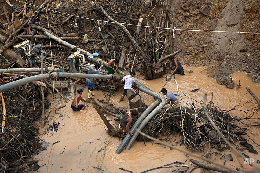 "In this May 5, 2014 photo, miners known as ""Maraqueros"" ready a rustic type of hydraulic jet known locally as a ""Chupadera,"" after hauling the device about 16-meters deep into a crater at a gold mine process in La Pampa in Peru's Madre de Dios region. A new threat now looms for the estimated 20,000 wildcat miners who toil in huge scar of denuded rainforest known as La Pampa, an area nearly three times the size of Washington, D.C. Peru's government declared all informal mining illegal on April 19 and began a crackdown. (AP Photo/Rodrigo Abd)"