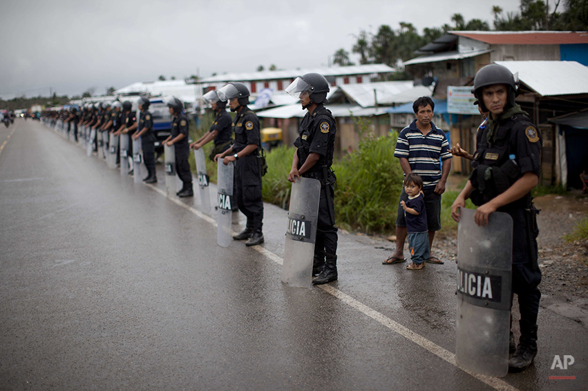 Police stand guard along a highway leading to illegal mining operations in La Pampa in the Madre de Dios region of Peru, Friday, May 16, 2014. The government started cracking down on illegal gold mining since a nationwide ban took effect April 19. (AP Photo/Rodrigo Abd)