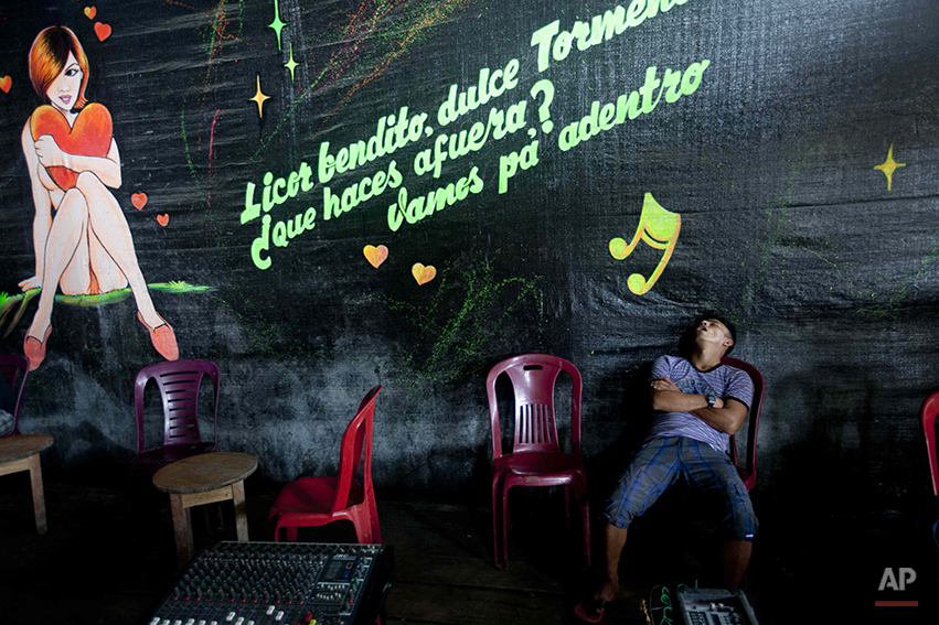 A man sleeps in a bar during a police operation that destroyed the illegal mining camp in La Pampa in the Madre de Dios region of Peru, Friday, May 16, 2014. Most miners are poor migrants from the Andean highlands. (AP Photo/Rodrigo Abd)