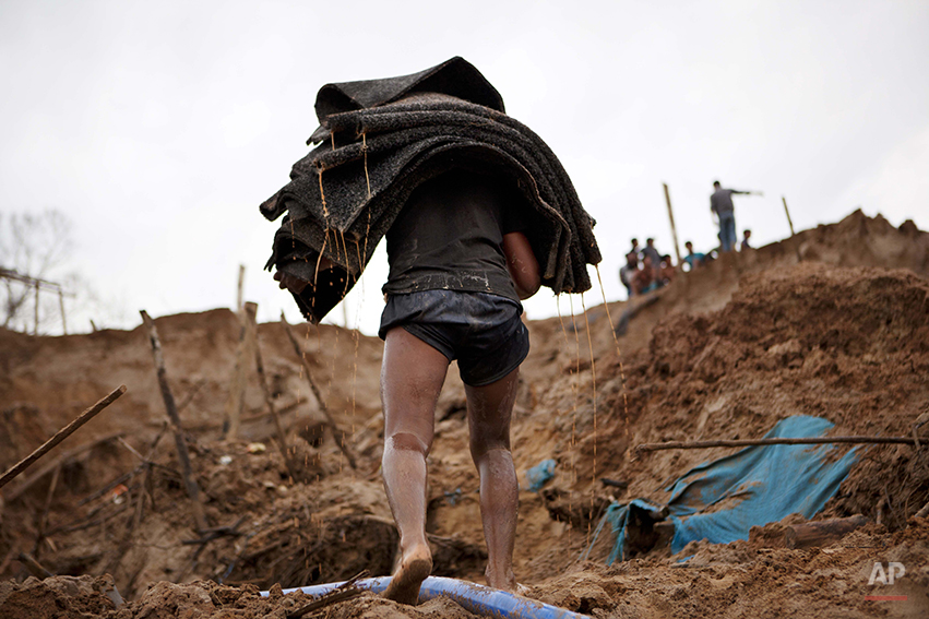 In this Friday, May 2, 2014 photo, a gold miner carries special carpets that are used to filter sand for gold at an illegal mine in La Pampa in the Madre de Dios region of Peru. Illegal mining accounts for about 20 percent of Peru's gold exports, and most miners are poor migrants from the Andean highlands. (AP Photo/Rodrigo Abd)