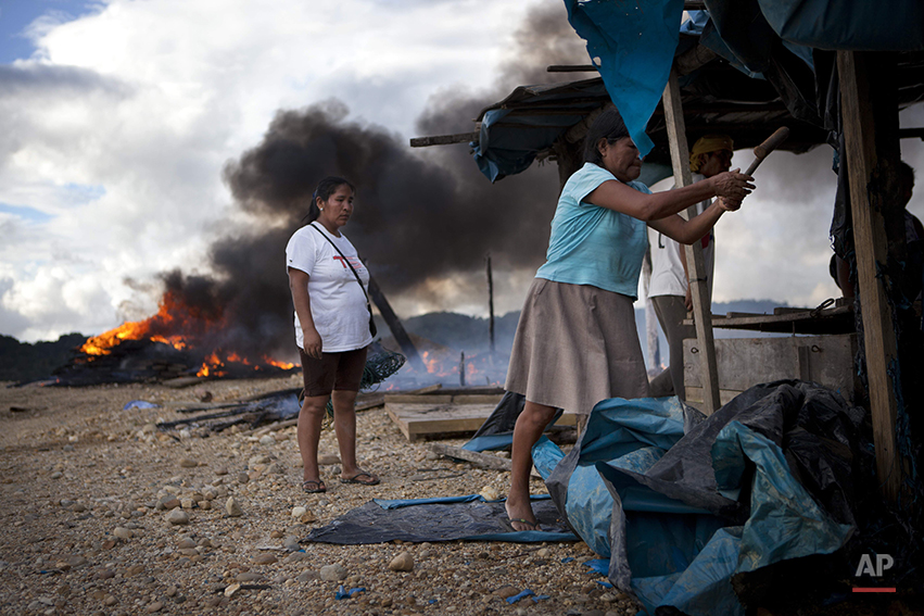 Women try to rescue some belongings after authorities blew up their illegal mining operation in Huepetuhe district in Peru's Madre de Dios region in Peru, Monday, April 28, 2014. Authorities began enforcing a ban on illegal mining Monday in the Huepetuhe district. They had given the state's illegal miners until April 19 to get legal or halt operations. Illegal mining accounts for about 20 percent of Peru's gold exports, but most miners are poor migrants from the Andean highlands. (AP Photo/Rodrigo Abd)
