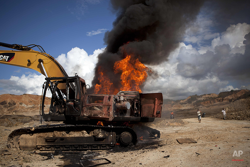A backhoe used for illegal mining burns after being destroyed by authorites in Huepetuhe district in Peru's Madre de Dios region in Peru, Monday, April 28, 2014. Authorities began enforcing a ban on illegal mining Monday in the Huepetuhe district. They had given the state's thousands of illegal miners until April 19 to get legal or halt operations. (AP Photo/Rodrigo Abd)