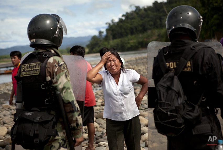 In this Wednesday, April 30, 2014 photo, a woman cries in front of police after authorities destroyed her canoe's engine, which partially destroyed her boat, for allegedly transporting machinery used by illegal gold miners at the Punkiri dock in Peru's Madre de Dios region. Illegal mining accounts for about 20 percent of Peru's gold exports, and most miners are poor migrants from the Andean highlands. The government started cracking down on illegal gold mining since a nationwide ban on illegal mining took effect April 19. (AP Photo/Rodrigo Abd)