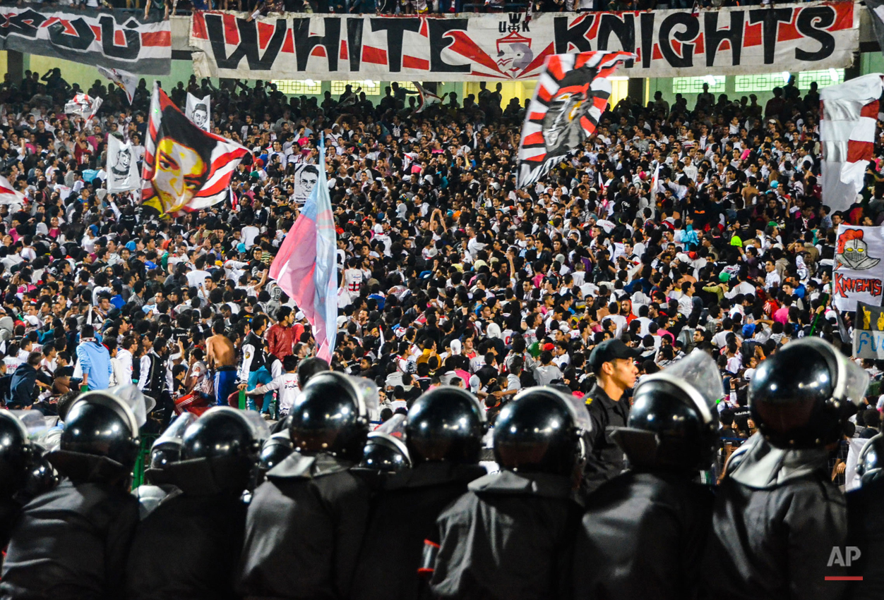 In this Feb. 9, 2014 photo, the Zamalek football clubís hardcore fan group Ultras White Knights (UWK) cheer as security forces stand guard during a soccer match between Zamalek and AS Douanes, during the Confederation of African Football (CAF) Champions League at the Cairo Stadium, in Egypt. Zamalek won 2-0. Banners with the face of a boy, depict Amr Hussein, 18, who was killed on Sept. 23, 2013, during clashes between the Ultras members and security forces. (AP Photo/Mohammed El Raai)