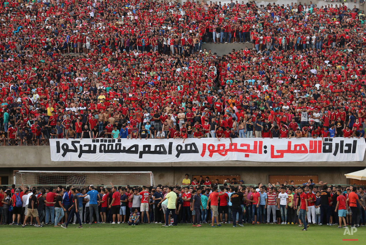 """In this July 19, 2015 photo, Ultras Ahlawy, the hardcore fan base of Al-Ahly football club,  watch players train at the Al - Ahly club in Cairo, Egypt. Ultras, whose name comes from the Latin word for ìbeyond,î started in Latin America and Europe in the 1950s and eventually made it to Arab countries, with particularly strong followings in North Africa. The first to form in Egypt, Ultras White Knights, emerged in 2007 to support the Zamalek team. Groups backing arch-rival al-Ahly and others soon followed. Arabic on the banner reads, """"the Al-Ahly administration: the fans are the most important group to be moved."""" (AP Photo/Mohammed El Raai)"""