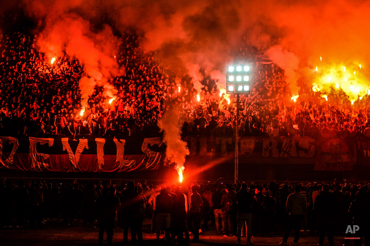 In this Feb. 1, 2015 photo, hardcore soccer fans known as Ultras Ahlawy, light flares and cheer during the third anniversary of people who were killed in the 2012 Port Said soccer riot, at Al -Ahly Sporting Club in Cairo, Egypt. On Feb. 1, 2012 over 70 people were killed in Port Said when Ahly fans were attacked by supporters of Port Said's football team Masry, who stormed the pitch at the end of the match. (AP Photo/Mohammed El Raai)